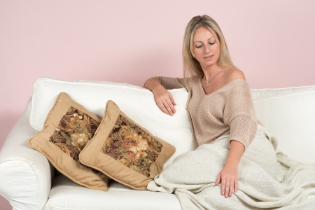 Sensual young woman in a sweater on a sofa with cushions photo