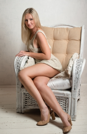 Smiling beautiful attractive woman in short dress is posing in a retro armchair