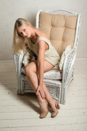 Smiling beautiful attractive woman in short dress is posing in a retro armchair Stock Photo - 14019891