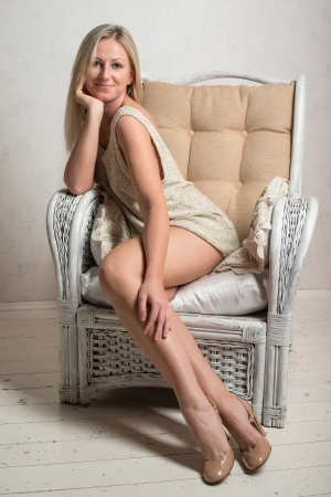 Smiling beautiful attractive woman in short dress is posing in a retro armchair photo