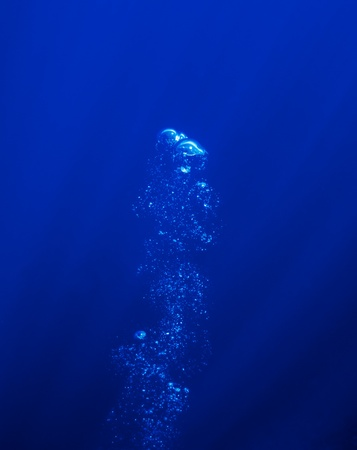 The picture shows underwater bubbles which raise from the depth of blue sea Stock Photo - 17101531