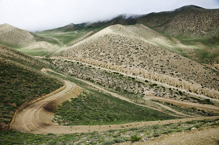 eminence: Clouds are moving down to the high mountain green valley along the meandering route from Ghemi to Lo Manthang, Upper Mustang, Nepal Stock Photo