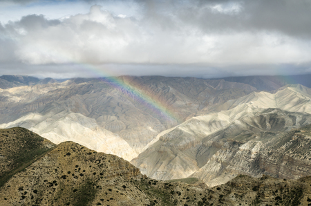happening: Real-colored rainbow in the high mountain sky after the distant rain along the route from Samar to Gemi villages of Upper Mustang, Nepal