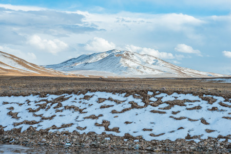 aloneness: Amazing Tibetan landscape with snowy mountains and cloudy sky at Qinghai province Stock Photo