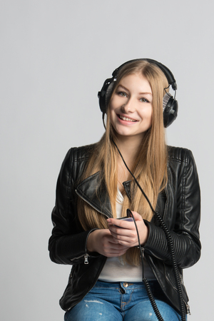 Adorable smiling girl in wired headphones is listening and enjoying music from her own smartphone