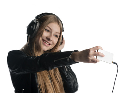 wired: Isolated on white happy face of a girl making selfie and a grimace while listening music in wired headphones Stock Photo