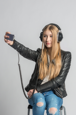 Young charming teenage girl is making selfie and listening music from personal mobile phone through wired headphones