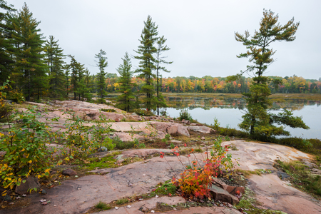 provincial forest parks: Typical Canadian landscape of a lake at Killarney Provincial Park with multicoloured fall trees and red rock formations Stock Photo