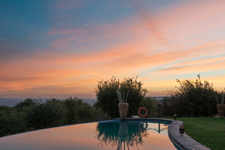 Morning colorful clouds and green Namibian trees are reflected in a mirror of a hotel swimming pool Stock Photo