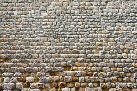 Frontal view of a broken textured ancient stone wall of a historical building