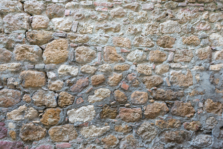 Close view of an aged cracked stone wall of a historical building