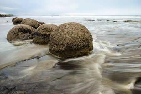 Impressive Moeraki boulders in the blurred Pacific Ocean waves