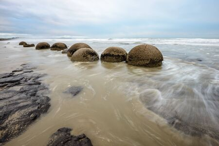 Impressive Moeraki boulders in the Pacific Ocean waves