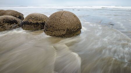 Moeraki boulders in the blurred Pacific Ocean waves Stock Photo