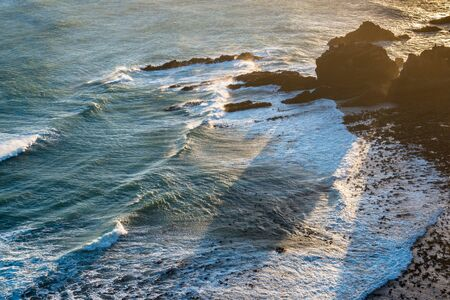 Sunset view of the Pacific Ocean waves at Nugget Point