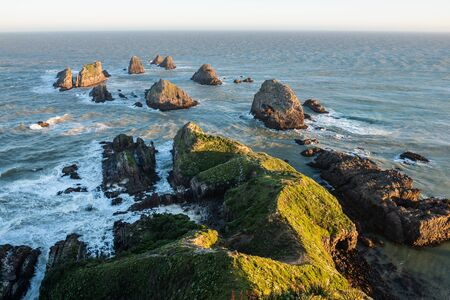 The setting sun illuminates boulders and waves of Nugget Point Stock fotó