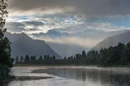 Bright ray of morning sun over the Lake Matheson