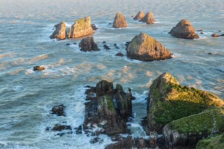 Setting sun illuminates boulders and waves of Nugget Point