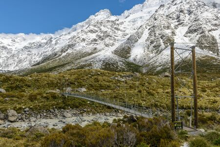 Snowy mountain scenery with scary hanging bridge at Hooker Valley Track, Mount Cook National Park, New Zealand