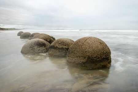 Impressive Moeraki boulders, cloudy morning sky and blurred Pacific Ocean waves at Moeraki Boulders Beach, New Zealand