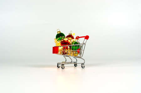 Shopping trolley with christmas balls and garlands. Plain background. Banco de Imagens
