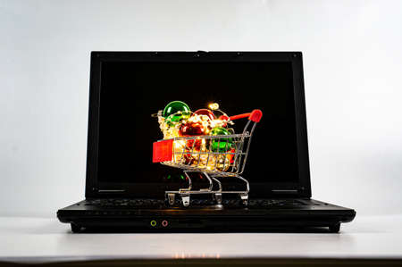 Shopping trolley with christmas balls and garlands on the keyboard of laptop. Plain background.