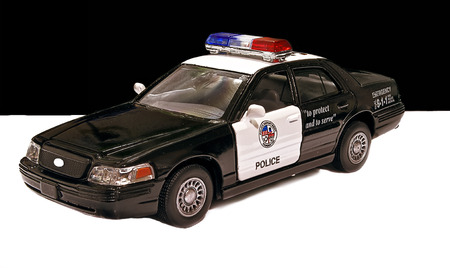 one object: Toy police car. Indoors. Horizontally. Color. Car model. Metal. One object. Shadow.