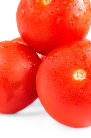 emphasis: Tomatoes with water drops on a white background. The group of objects is isolated on a white background. Small depth of sharpness. Emphasis of attention on forward tomato. Shadow. Indoors. Close up. Vertical format. Color.