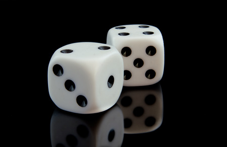 one object: Two game cubes on the black reflecting surface. One object is located ahead of another. Indoors. Horizontal format. Color. Photo.
