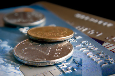 sharpness: Coins lie on cash cards against a dark background. Two coins lie on a bank plastic card. Small depth of sharpness. Emphasis of attention on a coin in the foreground. Coin advantage: two rubles. Blackout at the edges. Metal. Plastic. Yellow. Blue. Dark. In