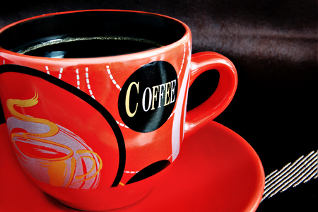 prevailing: Red cup with coffee against a dark background. A cup with a saucer close up. On a cup letters and drawings are represented. A background of dark brown color with light strips. Indoors. The prevailing color red and dark brown. Blackout at the edges. Photo. Stock Photo