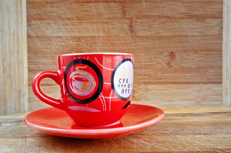two objects: Red cup and saucer on a wooden background. Two objects in interaction. Objects are made of ceramics. Color. Indoors. Horizontal format. Photo.