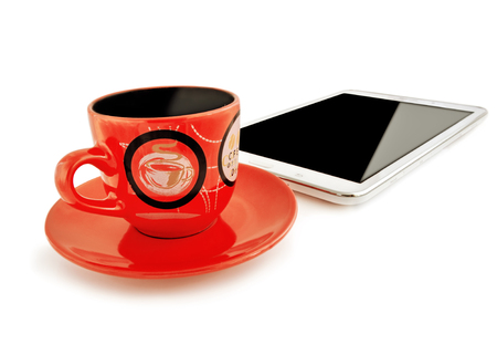 emphasis: Red cup with a saucer and the tablet computer on a white background. Two izoltrovannykh of object. The cup is located ahead of the tablet computer. The cup is made of ceramics. Emphasis of attention in the foreground. Horizontal format. Indoors. Natural l