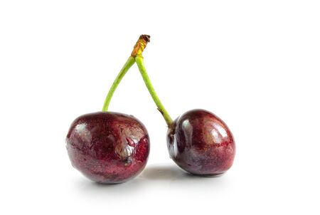 Two sweet cherries on a stalk.