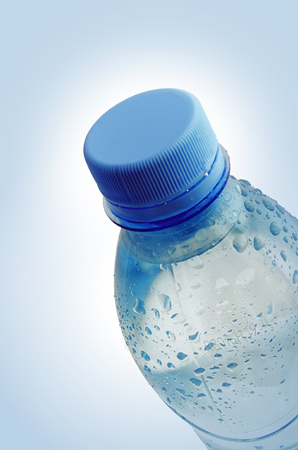 inclination: Water drops on a plastic bottle. The plastic bottle is located under an inclination. The bottle is closed by a cover. Vignette. Indoors. Vertical format. Color. Photo. Stock Photo