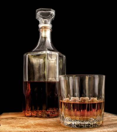 Glass with alcohol and a decanter on a black background. Vertical format. Indoors. Color. Photo.