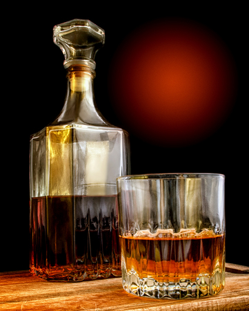 Glass and glass decanter with alcohol. A black background with a gradient with texture. Indoors. Vertical format. Color. Photo.