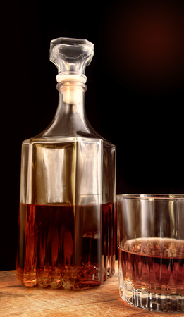 Glass decanter and glass with alcohol. Two objects against a dark background with a gradient. Indoors. Vertical format. Photo.