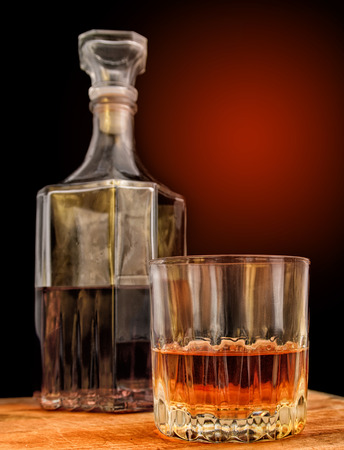 color photo: Glass with alcohol against the background of a decanter and a background with a gradient. Vertical format. Indoors. Color. Photo.