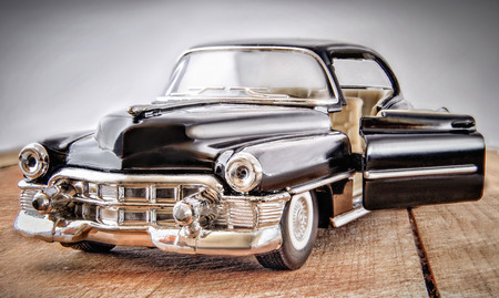 blackout: Car model. The car of black color with the chromeplated details. The car is located on wooden a surface. The door is open. Front view and sideways. Indoors. Horizontal format. Blackout at the edges. Color. Photo.