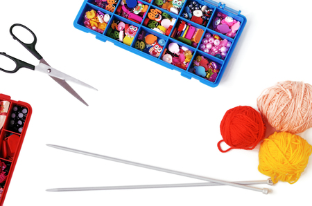 Accessories to knitting by spokes on a white background. Boxes with accessories, scissors, spokes. Top view. Horizontal format. Indoors. Color. Photo.