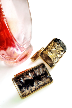 Cuff links and bottle of perfume on a white background. Two objects close up and fragment of a bottle of perfume. Indoors. Vertical format. Color. Photo.