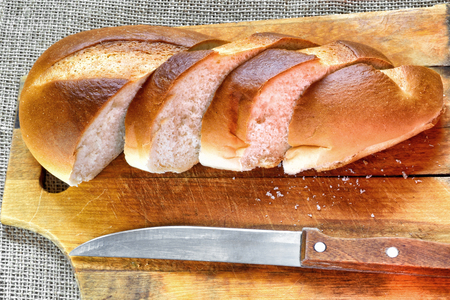 The bread cut by pieces and knife on a wooden chopping board. Top view. Horizontal format. Indoors. Color. Photo.