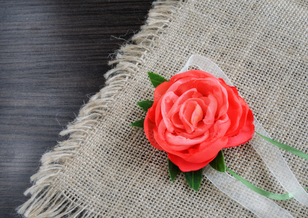 The decorative rose from fabric decorates burlap. Top view. Horizontal format. Indoors. Color. Photo.