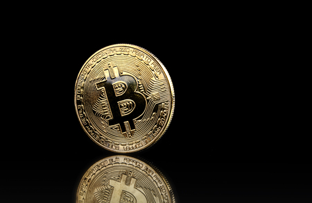 Cryptocurrency on a black background with reflection. The isolated object on a black background. Gold. Metal. Indoors. Color. Horizontal format. Photo.