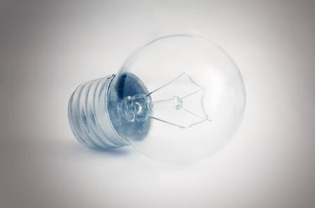 Glass electrical bulb on a light background with shading at the edges. Indoors. Toning. Horizontal format. Color. Photo.
