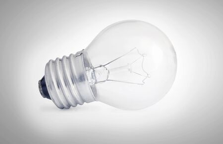 Glass light bulb on a light background with shading at the edges.  Indoors.  Toning.  Horizontal format.  Colour.   Photo. 写真素材