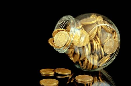 Yellow coins in a glass jar on a black background with reflection. Indoors. Horizontal format. Color. Photo. 写真素材 - 132069390