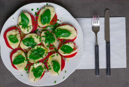 On a plate lies tomatoes, mozzarella cheese, basil and poured with olive oil Reklamní fotografie