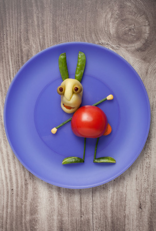 fun background: Vegetable rabbit on blue plate on wooden background Stock Photo